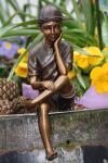 Bronzefigur Junge mit Baseballkappe, Skulptur aus Bronze, Kantenhocker