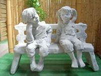 Steinfigur Mädchen und Junge auf Bank aus Steinguss