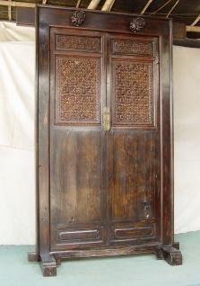 Die Vollholztür aus China ist in dunklem Holz gehalten und mit Schnitzereien verziert